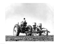 Low Angle View of a Farmer Planting Corn with a Tractor in a Field Fine Art Print
