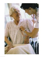 Female nurse checking a female patient's heartbeat Framed Print