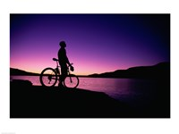 purple Silhouette of a man standing with mountain bike, Lake Powell, Utah Framed Print