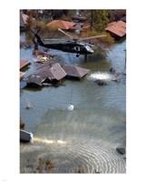 A Blackhawk helicopter drops sandbags into an area where the levee broke due to Hurricane Katrina Fine Art Print