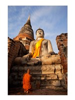 Monk praying in front of a statue of Buddha Fine Art Print