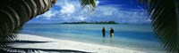 Rear view of two native teenage girls in lagoon, framed by palm tree, Aitutaki, Cook Islands. Fine Art Print