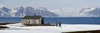Two hikers standing on the beach near a hunting cabin, Bellsund, Spitsbergen, Svalbard Islands, Norway Fine Art Print
