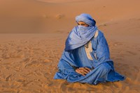 Veiled Tuareg man sitting cross-legged on the sand, Erg Chebbi, Morocco Fine Art Print