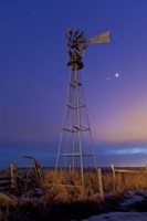 Venus and Jupiter are visible behind an old farm water pump windmill, Alberta, Canada Framed Print