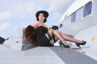 Glamorous woman in 1940's style attire sitting on a vintage aircraft Fine Art Print