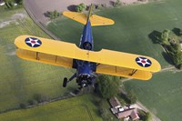 Boeing Stearman Model 75 Kaydet flying over fields Fine Art Print