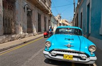 Cuba, Camaquey, Oldsmobile car and buildings Fine Art Print