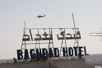 An AH-64 Apache in flight over the Baghdad Hotel in central Baghdad, Iraq Fine Art Print