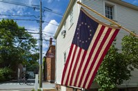 New Hampshire, Portsmouth, Strawberry Banke Historic Area, building with US flag Fine Art Print
