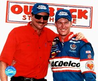 Dale Earnhardt standing with Dale, Jr, steakhouse sign in background