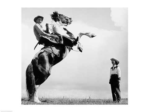 Framed Low angle view of a cowboy riding a bucking horse Print