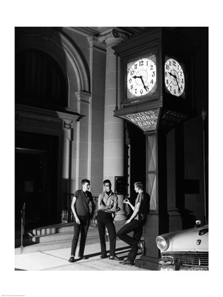 Framed Young men standing below clock at night Print