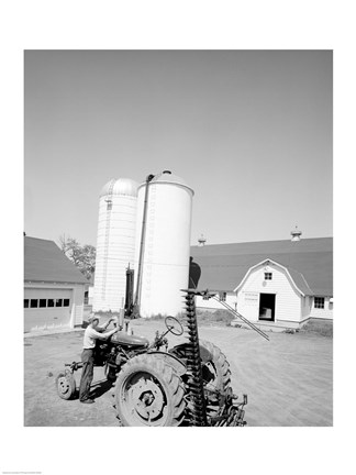 Framed USA, Farmer Working on Tractor, Agricultural Buildings in the Background Print