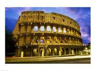 Low angle view of the old ruins of an amphitheater lit up at dusk, Colosseum, Rome, Italy Art
