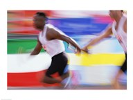 Side profile of two young men passing a relay baton