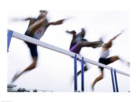 Low angle view of three men jumping over a hurdle
