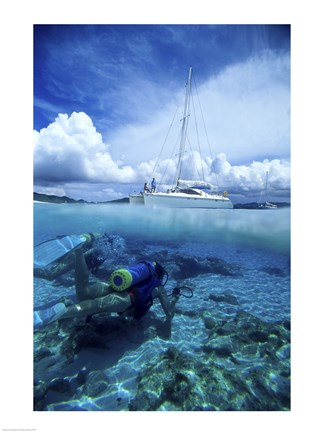 Framed Scuba diver in the water with a sail boat in the background, British Virgin Islands Print