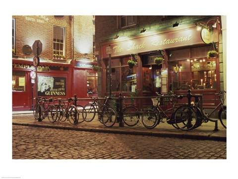 Framed Bicycles parked in front of a restaurant at night, Dublin, Ireland Print