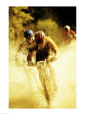 Framed Young men riding bicycles through water Print