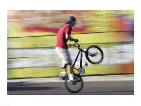 Framed Side profile of a teenage boy performing a stunt on a bicycle Print