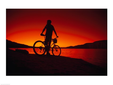 Framed Silhouette of a man standing with a bike, Lake Powell, Utah Print