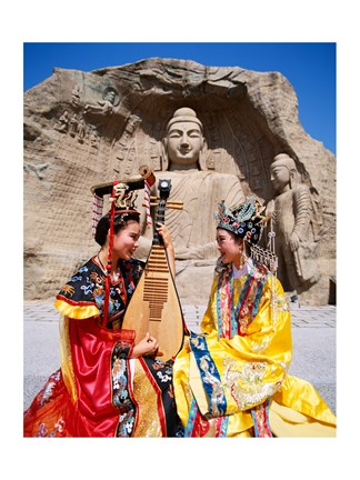 Framed Two girls in traditional costumes in front of the Buddha Statue, China Print