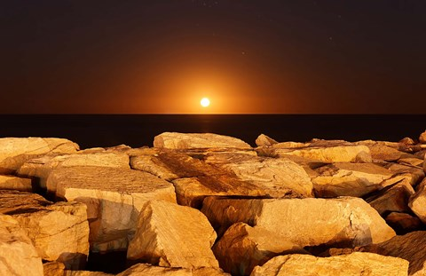 Framed moon rising behind rocks lit by a nearby fire in Miramar, Argentina Print