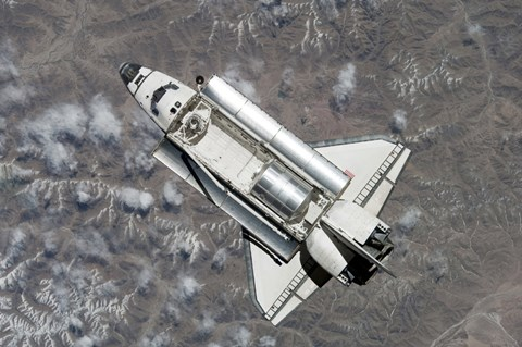 Framed Aerial view of Space Shuttle Discovery over Earth as it approaches the International Space Station Print