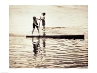 Two boys standing on a wooden platform in a lake - various sizes