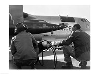 Rear view of two men crouching near fighter planes, X-15 Rocket Research Airplane, B-52 Mothership - various sizes