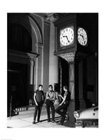Young men standing below clock at night - various sizes