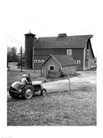 Man with a Boy Riding a Tractor in a Field Framed Print