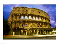 Low angle view of the old ruins of an amphitheater lit up at dusk, Colosseum, Rome, Italy Fine Art Print