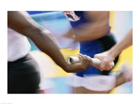 Mid section view of runners exchanging baton at a relay race Fine Art Print
