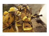 Side profile of a group of firefighters holding water hoses - various sizes