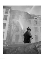 Firefighter pouring water on burning building, low angle view Fine Art Print