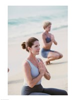 Young woman and a mid adult woman meditating on the beach - various sizes