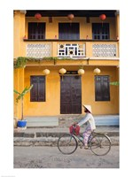 Person riding a bicycle in front of a cafe, Hoi An, Vietnam - various sizes
