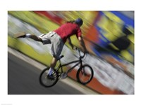 Rear view of a teenage boy performing a stunt on a bicycle Framed Print