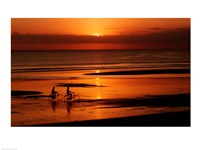 Silhouette of a young couple cycling on the beach - various sizes
