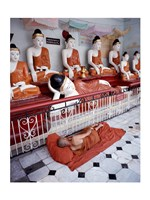 Monk Sleeping in Front of Buddha Statues Fine Art Print