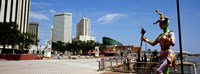 """Jester statue with buildings in the background, Riverwalk Area, New Orleans, Louisiana, USA by Panoramic Images - 36"""" x 12"""""""