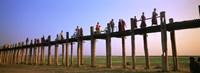 """Myanmar, Mandalay, U Bein Bridge, People crossing over the bridge by Panoramic Images - 27"""" x 9"""""""