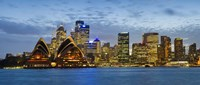 """Opera house and buildings lit up at dusk, Sydney Opera House, Sydney Harbor, Sydney, New South Wales, Australia by Panoramic Images - 27"""" x 9"""""""