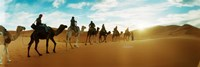 Tourists riding camels through the Sahara Desert landscape led by a Berber man, Morocco Fine Art Print