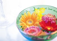 """Pink, orange and yellow flowers floating in a blue bowl by Panoramic Images - 36"""" x 26"""""""