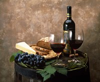 Still life of wine bottle, wine glasses, cheese and purple grapes on top of barrel Fine Art Print