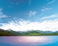 """Pink light cast down on two rings in lavender water with deep blue sky and clouds over green mountains in distance by Panoramic Images - 24"""" x 20"""""""