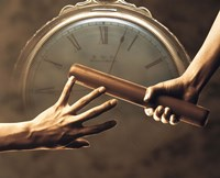 """Close up of two runners hands passing the baton in relay race in front of old European clock face by Panoramic Images - 16"""" x 13"""""""